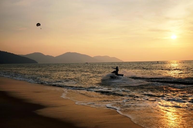 Jet skiing at Batu Ferringhi Beach, Penang, as the sunsets.